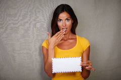 Surprised lady holding letter with hand to mouth Stock Images