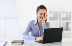 Surprised laughing business woman withvlaptop in the office. Background Royalty Free Stock Image