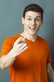 Surprised lächelnder sportlicher Mann, der etwas mit Index zeigt Lizenzfreie Stockfotografie