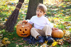 Surprised little boy with halloween pumpkins Stock Images