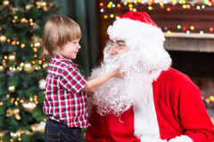 Surprised little boy looks at fake Santa Claus Royalty Free Stock Photography