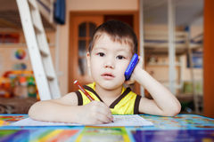 Surprised little boy talking on smartphone at home stock photos