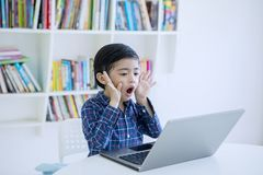 Free Surprised Little Boy Using A Laptop In The Library Stock Images - 157341904