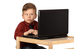Surprised little boy working on a laptop computer. Isolated on white background Stock Photo