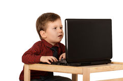 Surprised little boy working on a laptop. Computer isolated on white background Royalty Free Stock Image