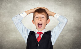 Surprised little businessman on irregular gray wall Royalty Free Stock Photos