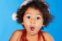 Surprised little child in Christmas hat. Against blue background stock photography