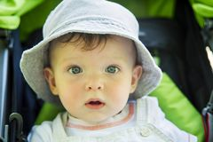 Surprised little child in green stroller. portrait royalty free stock image