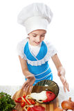 Surprised little cook dropping a plate with salad Stock Photos