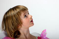 Surprised little fairy. Cute toddler girl in a fairy dress looking upwards with an expectant expression on her face Royalty Free Stock Image