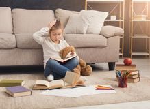 Surprised little female child hugging her teddy bear and reading. Surprised little casual girl embracing teddy bear and reading book. Pretty kid at home, sitting Stock Images