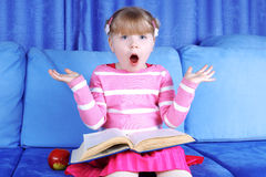 Surprised little girl with apple and book Stock Photo