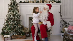 Surprised little girl checking upon Santa beard stock video