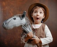 Surprised little girl dressed like a cowboy playing with a homem. Ade horse. Expressive facial expressions Stock Photos