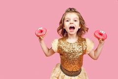 Little girl in dress with donuts royalty free stock image