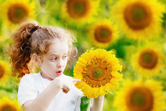 Surprised little girl hold the head sunflower. Healthcare, medic Stock Photos