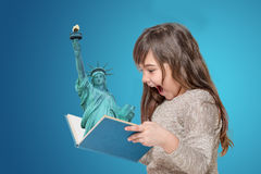 Free Surprised Little Girl Holding Open Book With Lady Liberty Stock Image - 90653961