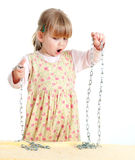 Surprised little girl keeping chains Stock Photo