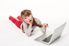 Surprised little girl lying on stomach on the floor with laptop Stock Photo