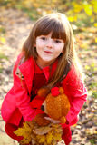 Surprised little girl with maple leaves and bear Stock Image