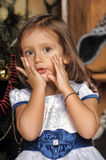Surprised little girl near the Christmas tree Royalty Free Stock Image