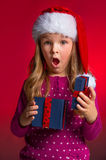 Surprised little girl with open gift box. Stock Photo