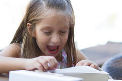 Surprised little girl opens a giftbox Royalty Free Stock Images