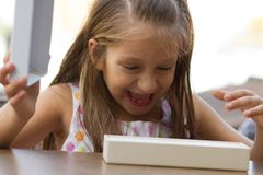 Surprised little girl opens a present Stock Photography