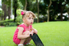Surprised little girl outdoor with tablet pcм on Stock Photography