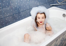 Surprised little girl sitting in a bath with soap suds Stock Image
