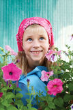 Surprised little girl sitting in the garden on a background of p Stock Photos