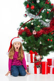 Surprised little girl sitting in Santa hat under new year tree. Stock Photo