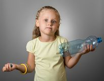 Surprised little girl is standing with an empty bottle, on gray stock image