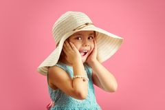 Surprised little girl in straw hat and blue dress, puts her hands to face, expresses surprise, opened her mouth wide royalty free stock photography