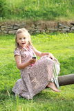 Surprised little girl on a swing. Barefoot little girl in a flowered dress surprised while holding a mobile phone on a swing Royalty Free Stock Photo