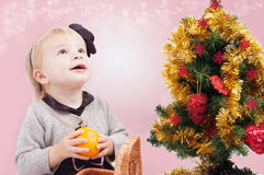 Surprised little girl under Christmas tree Royalty Free Stock Images