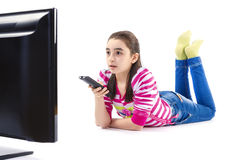 Surprised little girl watching tv. Little girl with remote control watching LED tv laying on white background Stock Photos