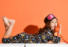 Free Surprised Little Kid Girl In Pajamas With Kittens Print Is Lying On Her Stomach, Talking By Phone On Orange Stock Photo - 159347870