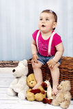 Surprised little toddler sitting on the basket with plush toys Stock Photography