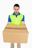 Surprised looking delivery man handing over parcel Royalty Free Stock Image