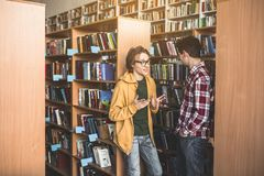 Serene comrades telling in athenaeum. Surprised male talking with orderly groupmate while gesticulating hands. He leaning against bookshelf in library Royalty Free Stock Photo