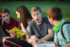 Surprised Male Teen with Friends. Surprised young student with group of friends outdoors Royalty Free Stock Photography