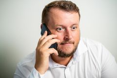 Surprised male in white shirt is talking on the phone on a white gray background royalty free stock photography