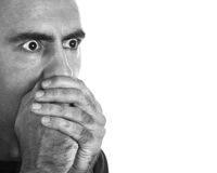 Surprised Man. Surprised or scared young man covering his mouth with his hands Royalty Free Stock Photography