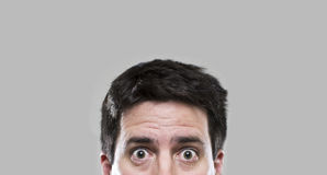 A surprised man. A man peeks into the bottom of the frame Royalty Free Stock Image