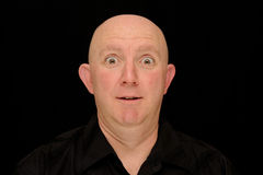 Surprised man. A bald man with a surprised expression stock photo