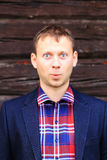 Surprised man in blue jacket and checkered shirt. On wood background Stock Photography