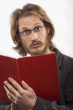 Surprised Man With a Book. Young blond handsome man wearing glasses is very surprised after reading a book. Shot in studio. Isolated over white Royalty Free Stock Image