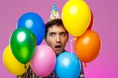 Surprised man celebrating birthday, holding colorful baloons over purple background. Stock Image