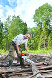The surprised man with a chain saw in summer wood Royalty Free Stock Photography